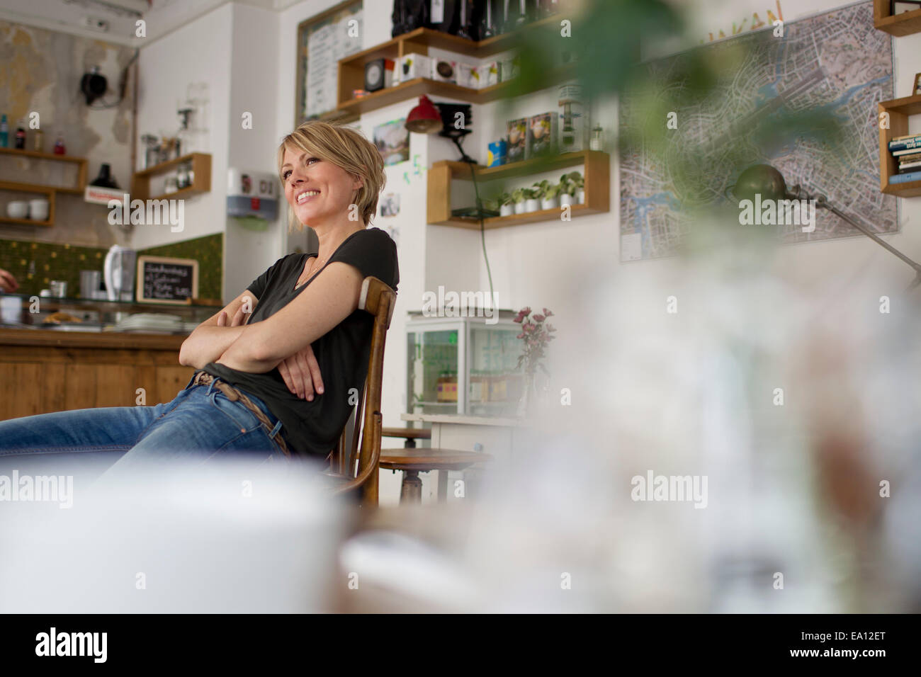 Mid adult woman sitting in cafe - Stock Image