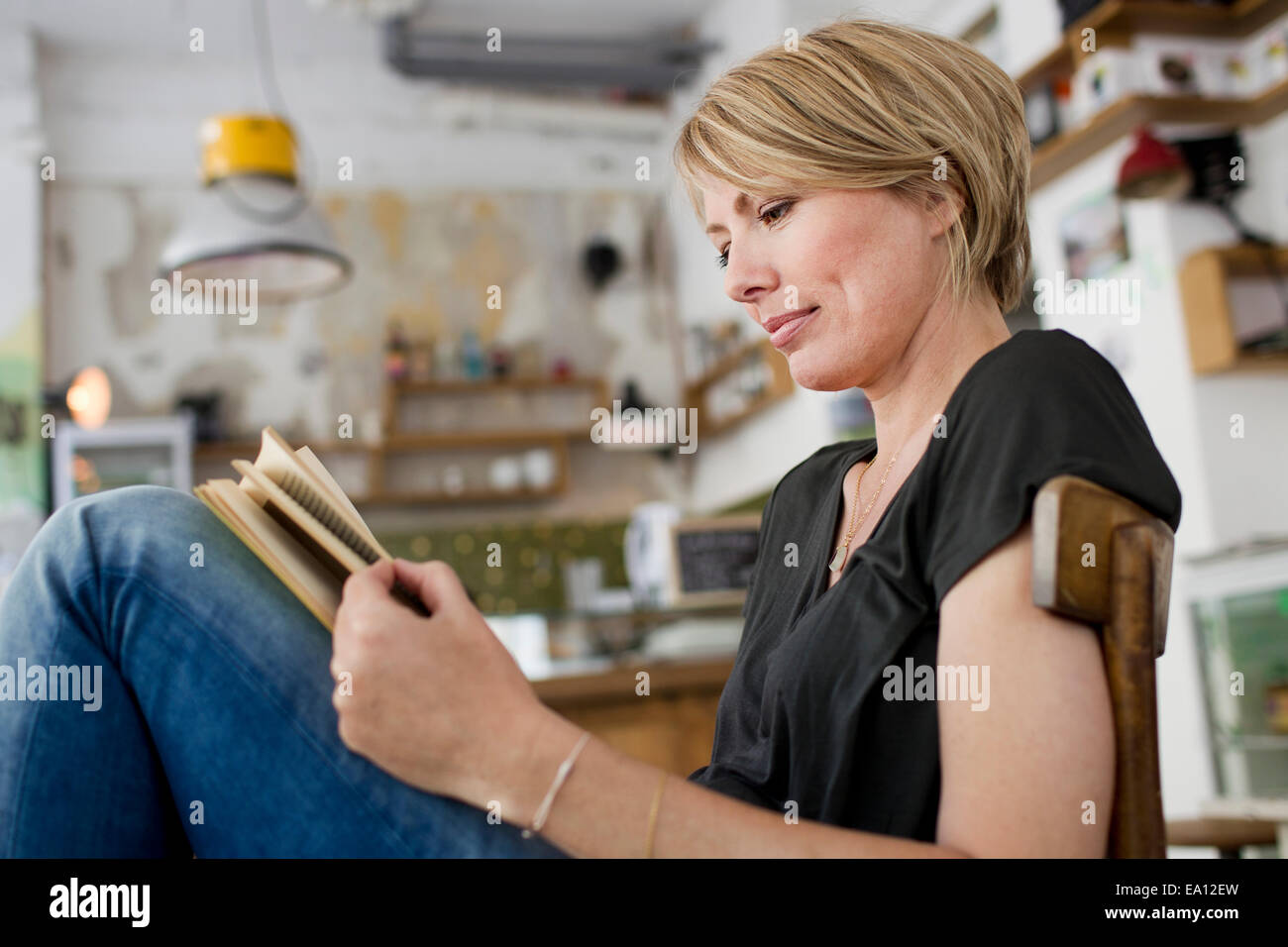 Mid adult woman reading book in cafe Stock Photo