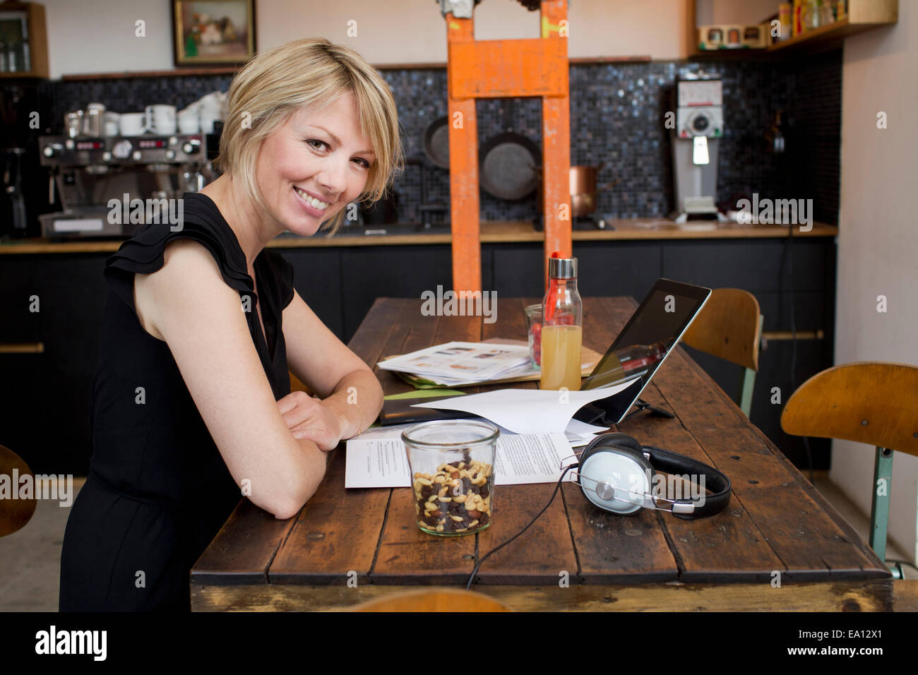 Mid adult woman in cafe with paperwork - Stock Image