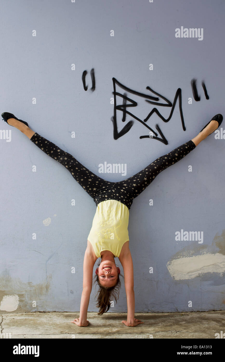 Teenage girl doing handstand against wall - Stock Image