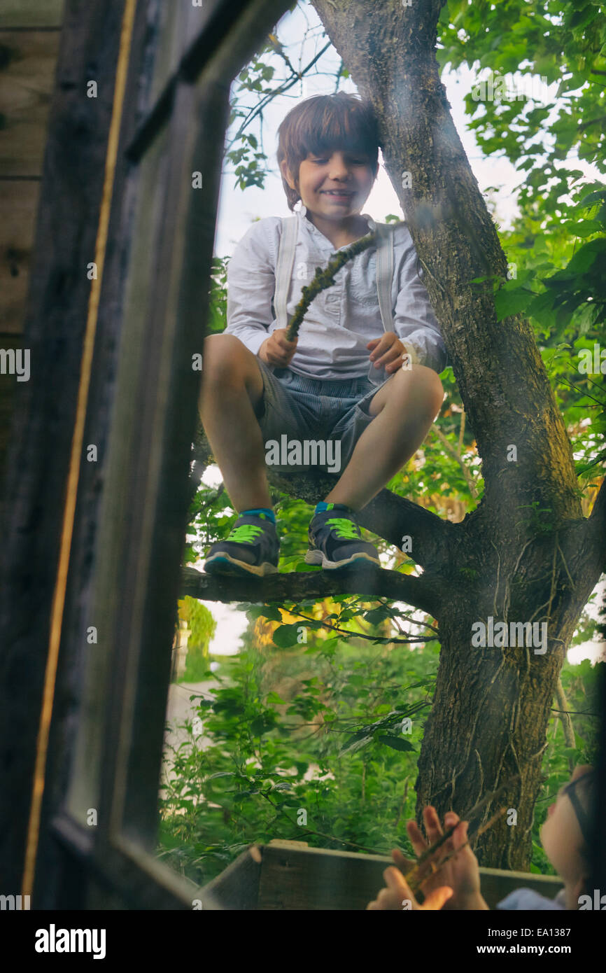 Two boys playing in tree outside hut window - Stock Image