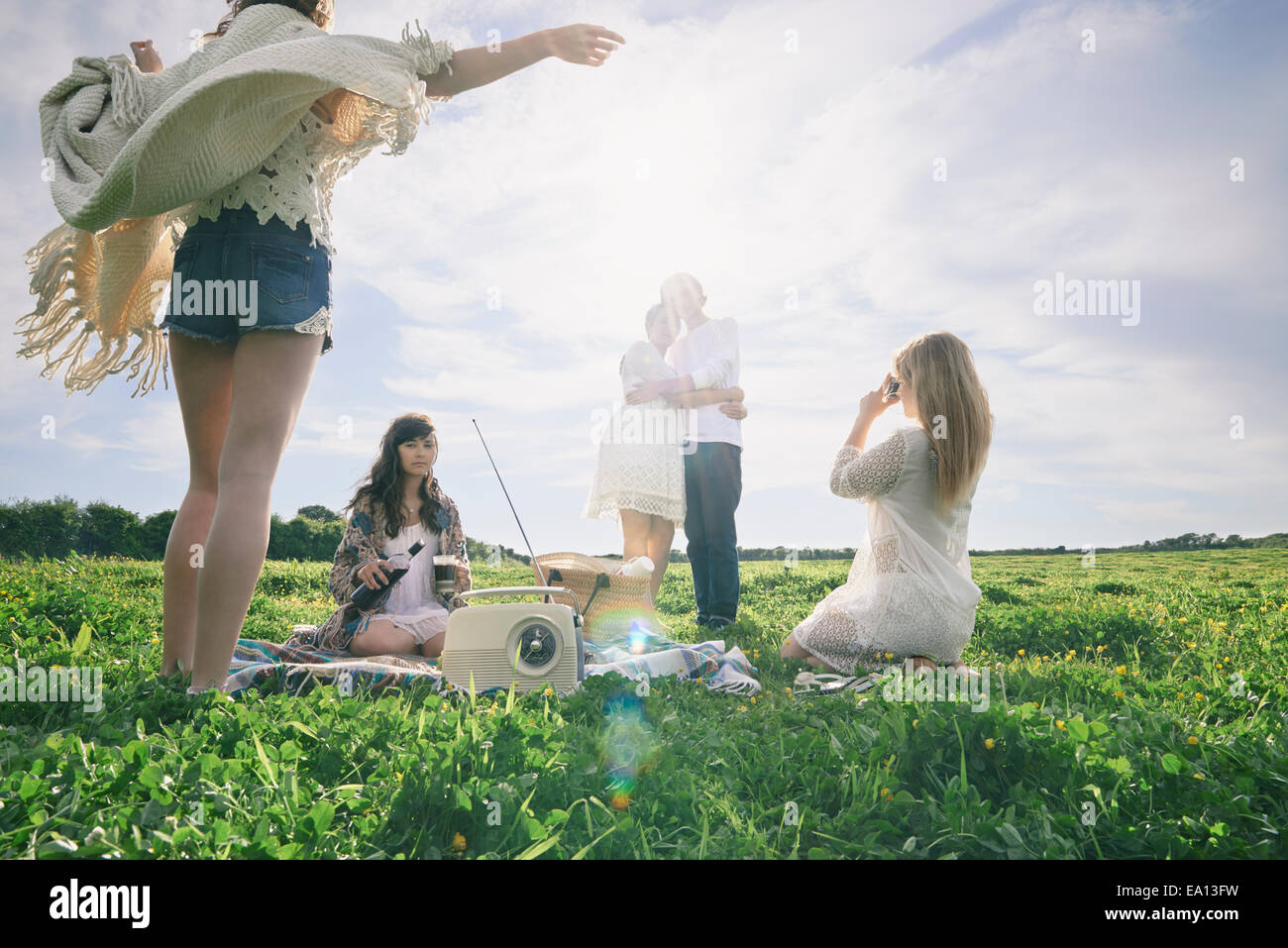 Five young adult friends having a picnic in field - Stock Image