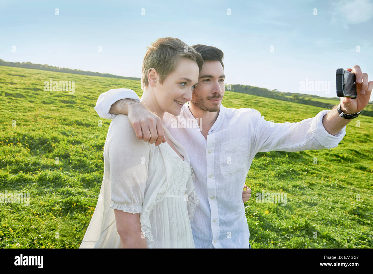 Young couple in field posing for selfie on smartphone - Stock Image