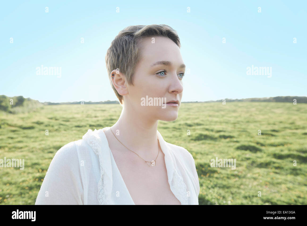 Portrait of young woman gazing in field - Stock Image
