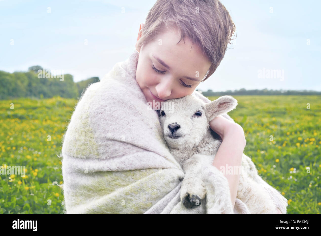 Portrait of young woman in field carrying lamb and wrapped in blanket Stock Photo