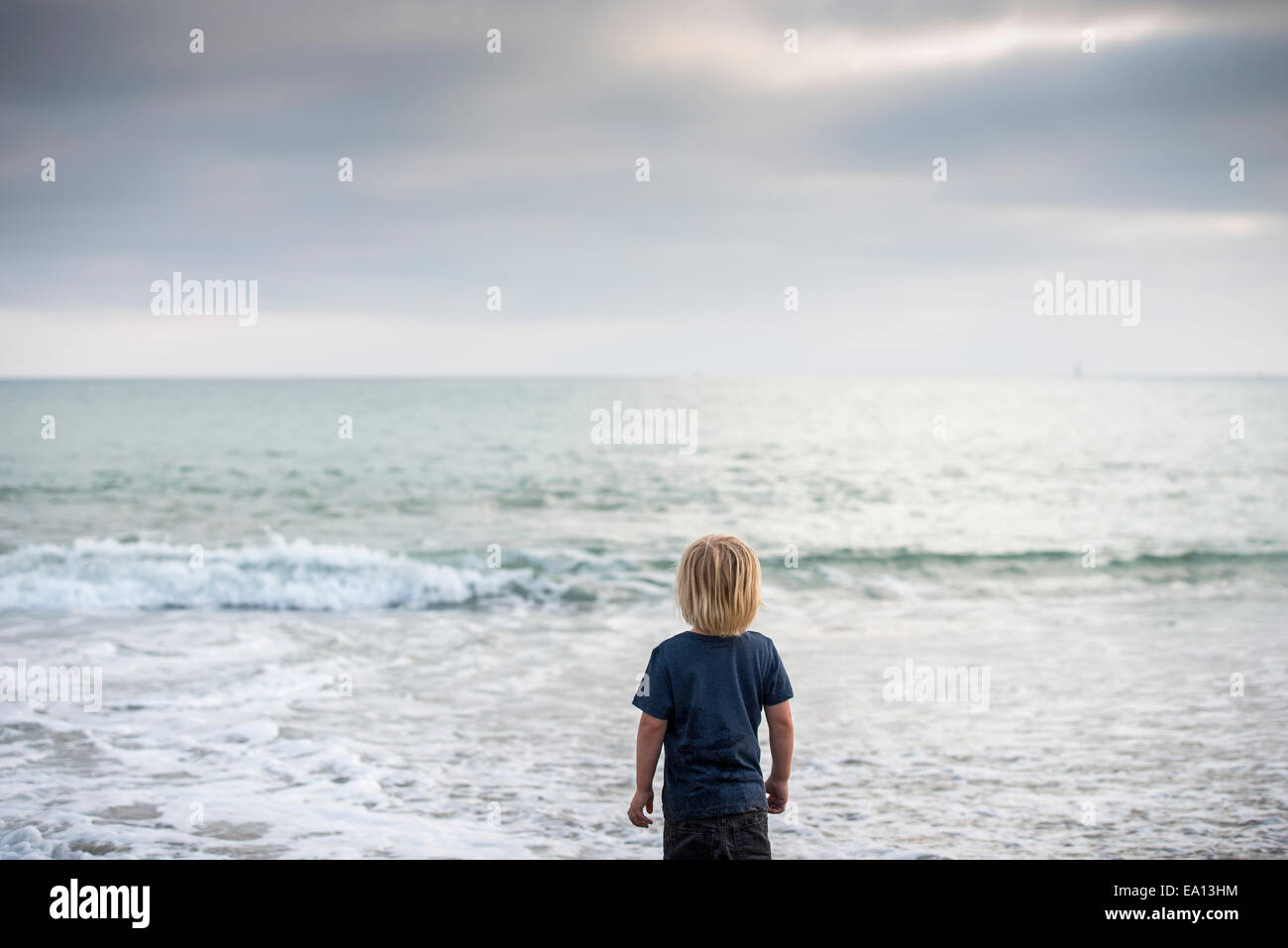Rear view of boy gazing out to sea, Dana Point, California, USA - Stock Image