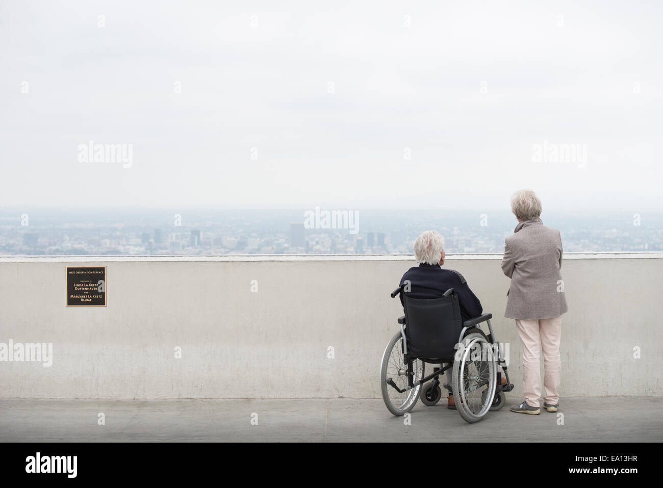 Rear view of senior man in wheelchair and his wife looking at city from viewing balcony Observatory Griffith Park Stock Photo