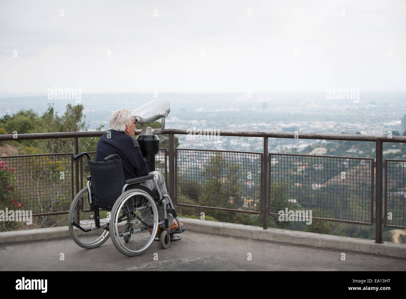 Senior man in wheelchair looking at city through coin operated binoculars from viewing balcony Observatory Griffith - Stock Image