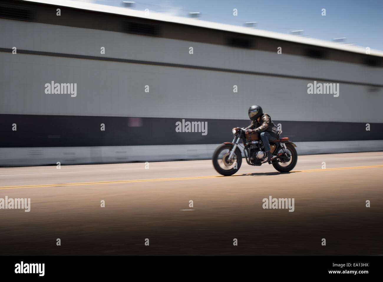 Blurred image of speeding male motorcyclist - Stock Image