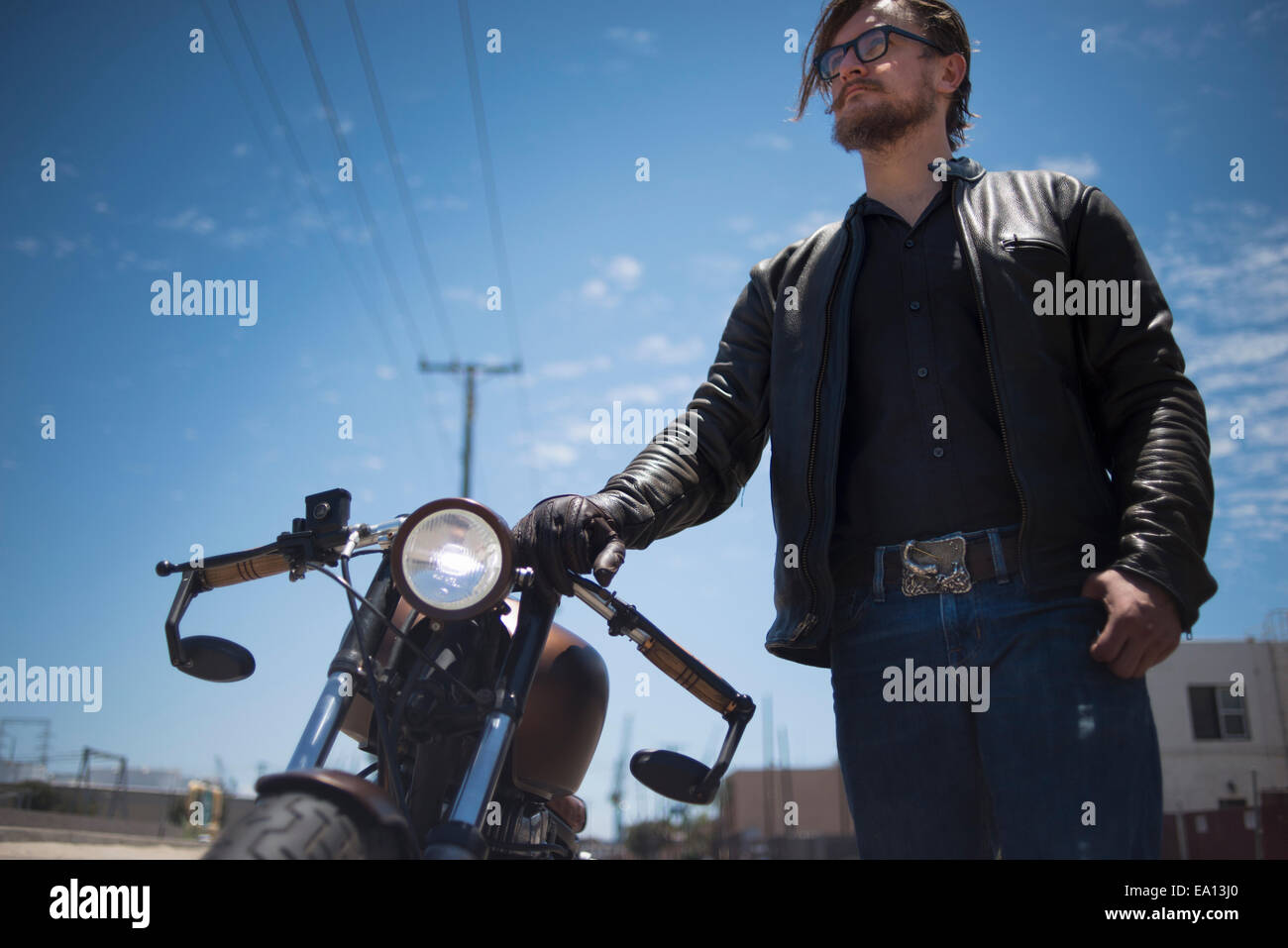 Low angled portrait of male hipster motorcyclist - Stock Image