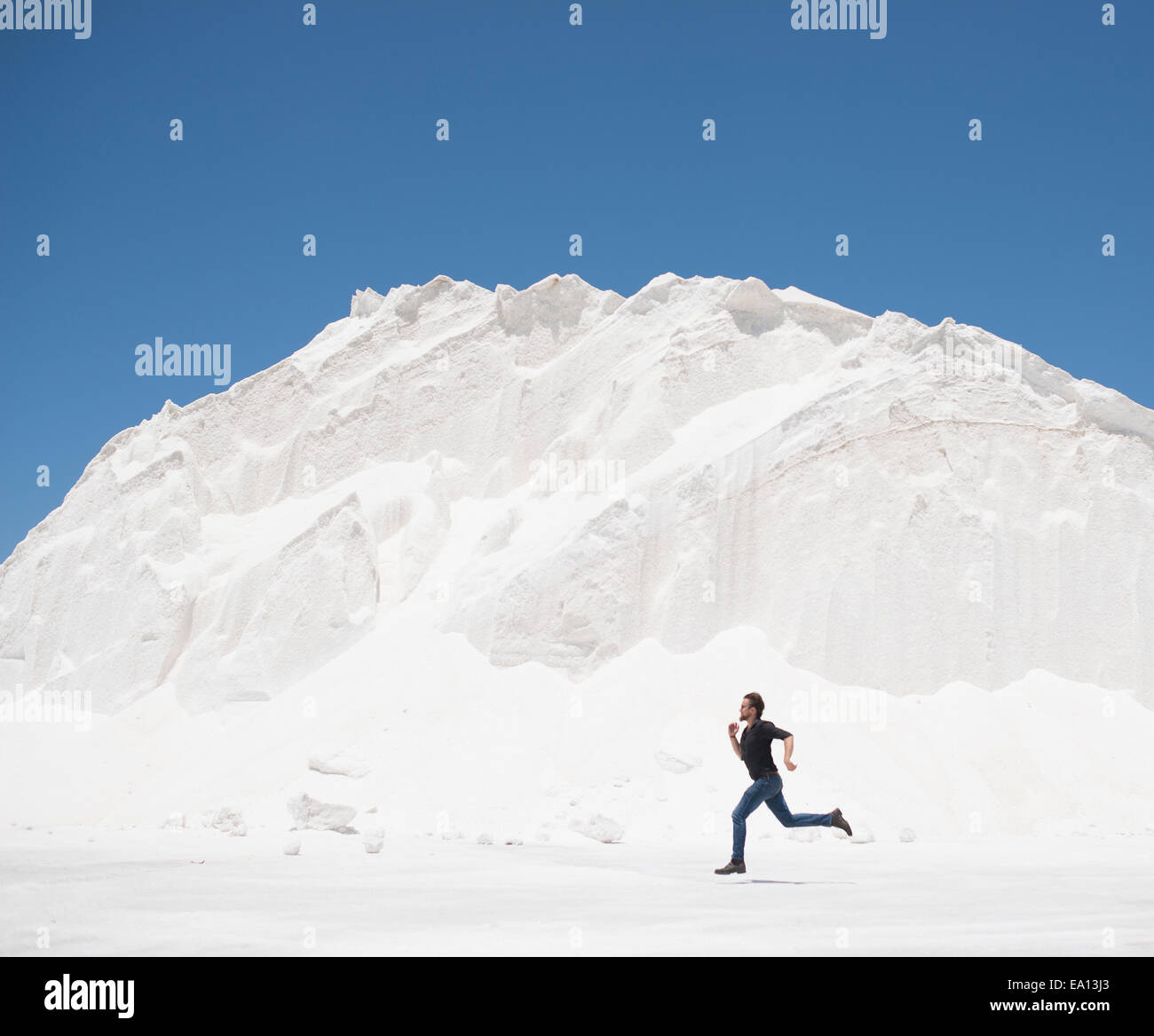 Man running in front of white mountain - Stock Image