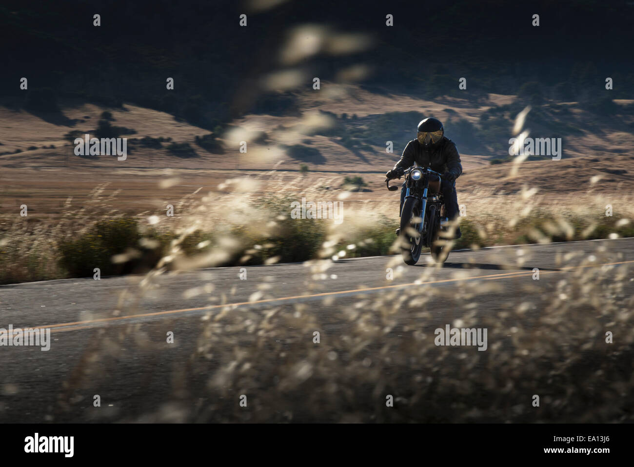 Male motorcyclist riding on highway - Stock Image