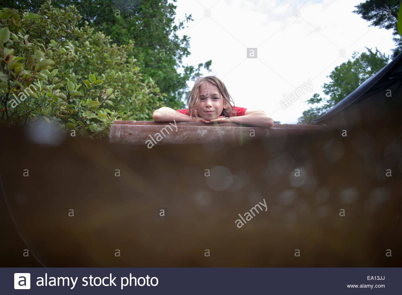 Portrait of girl resting on hands on top of roof - Stock Image