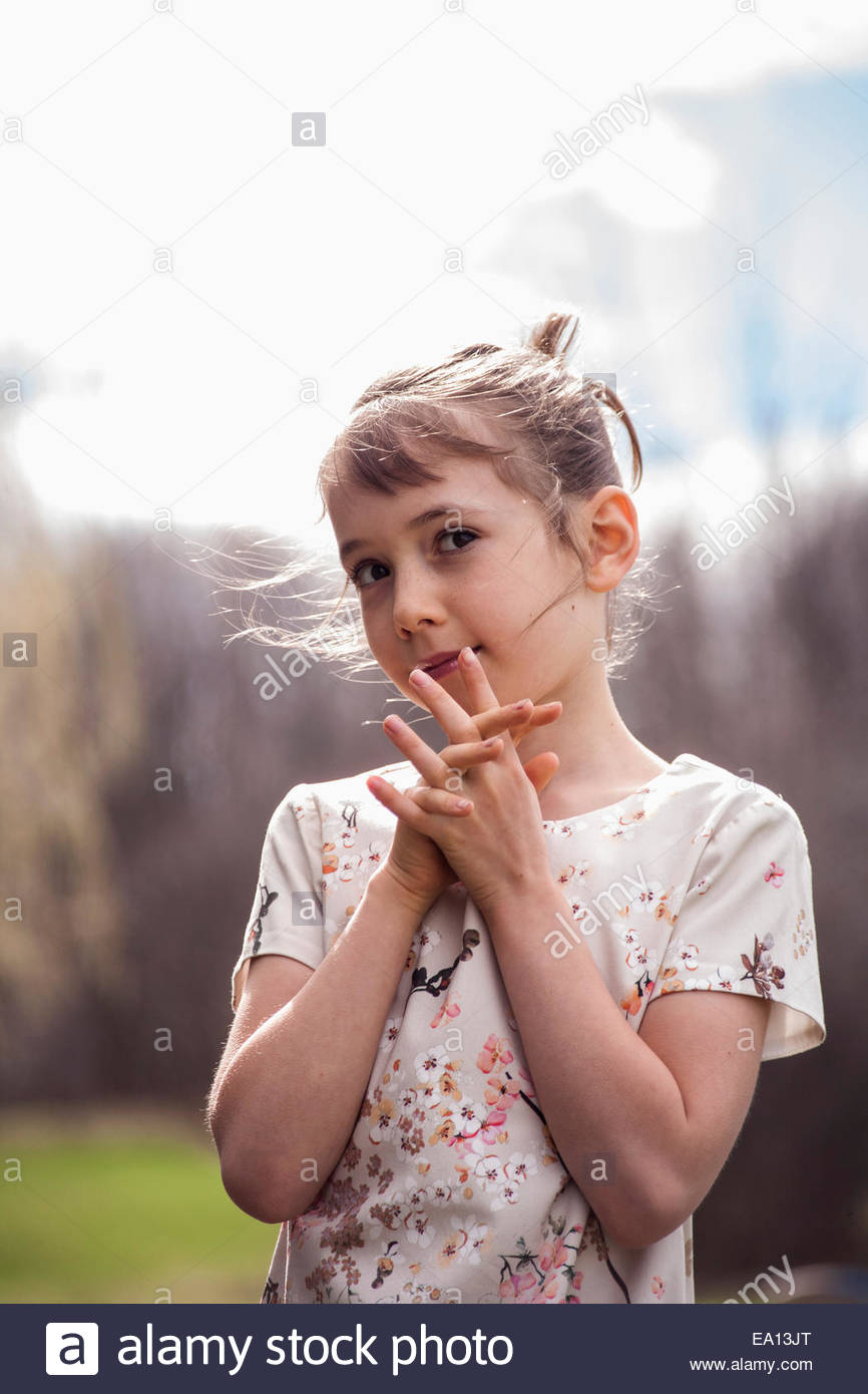 Portrait of pretty girl with fingers entwined - Stock Image