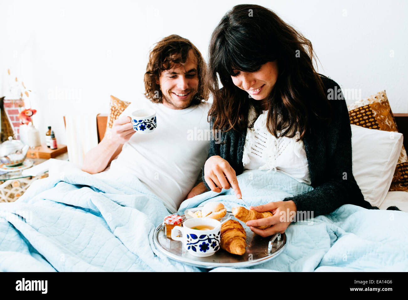 Couple having breakfast in bed - Stock Image