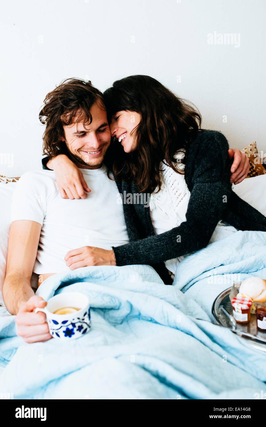 Couple having breakfast in bed - Stock Image