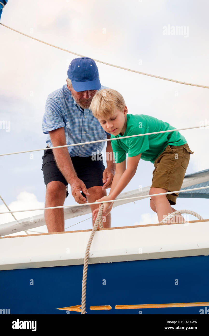 Boy helping grandfather pull ropes on sailboat - Stock Image