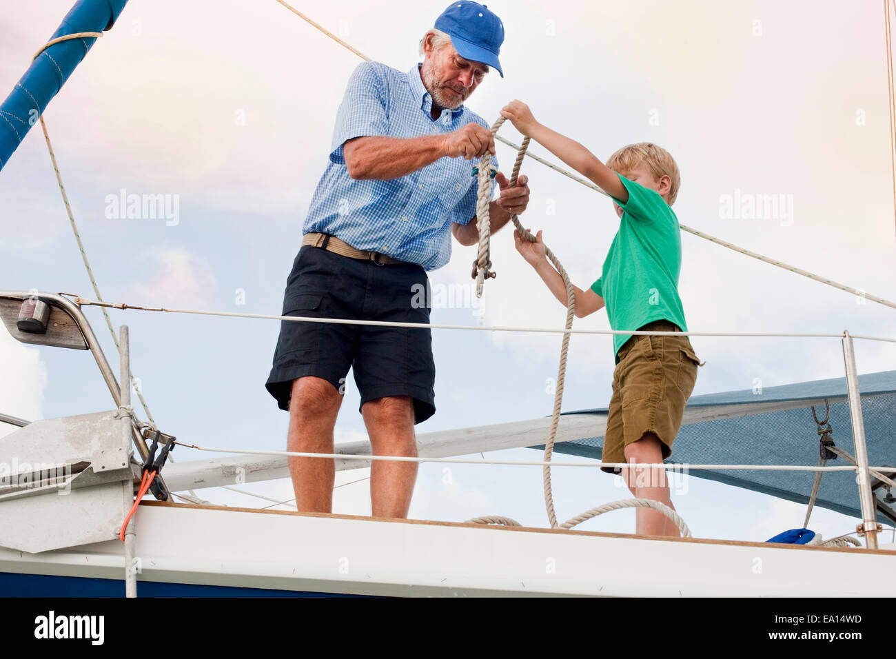 Boy and grandfather knotting rope on sailboat - Stock Image