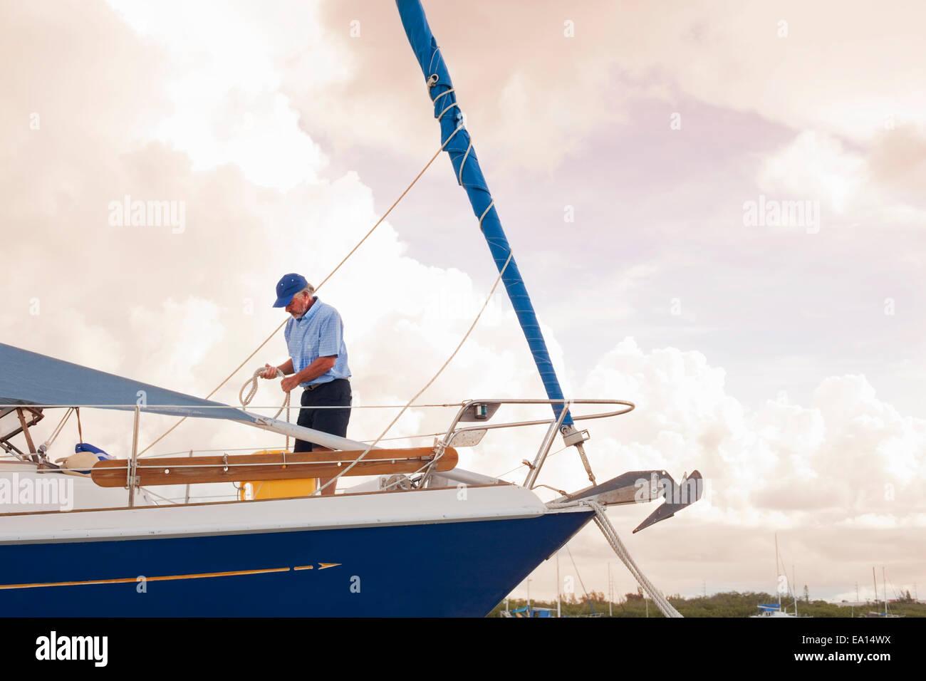 Senior man checking ropes on sailboat - Stock Image