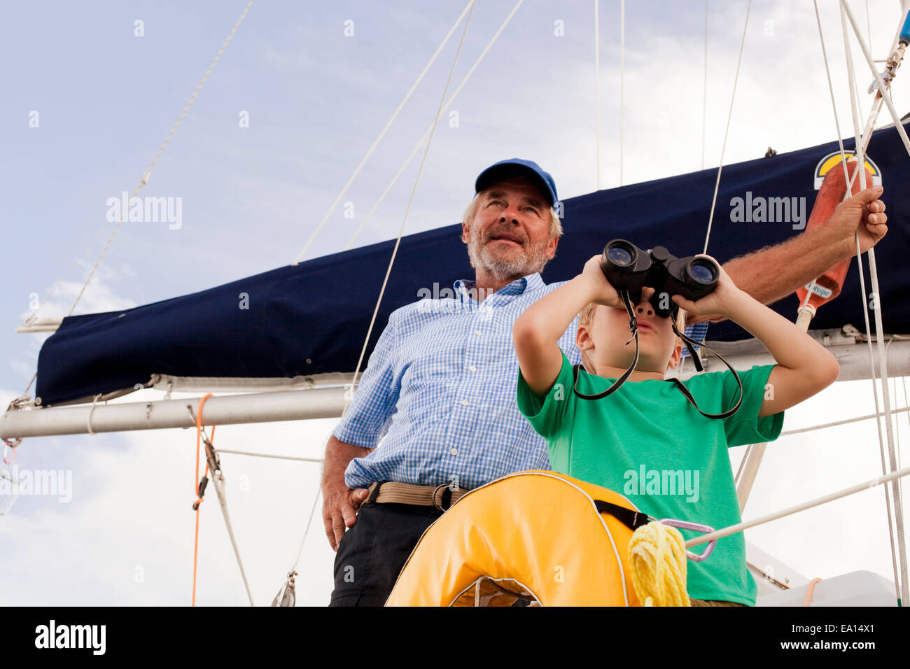 Boy and grandfather on sailboat looking through binoculars - Stock Image