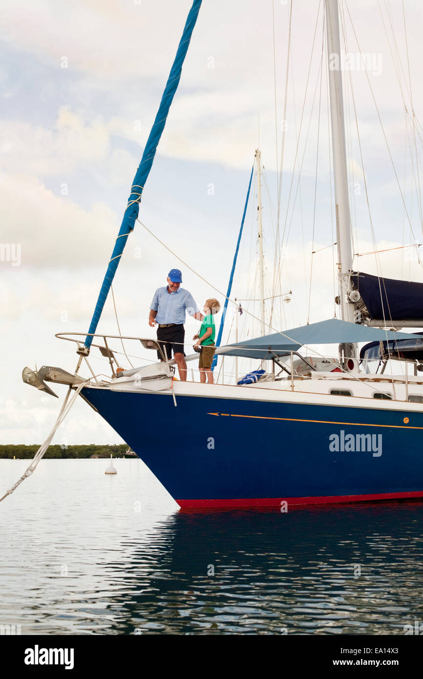 Boy and proud grandfather on sailboat - Stock Image