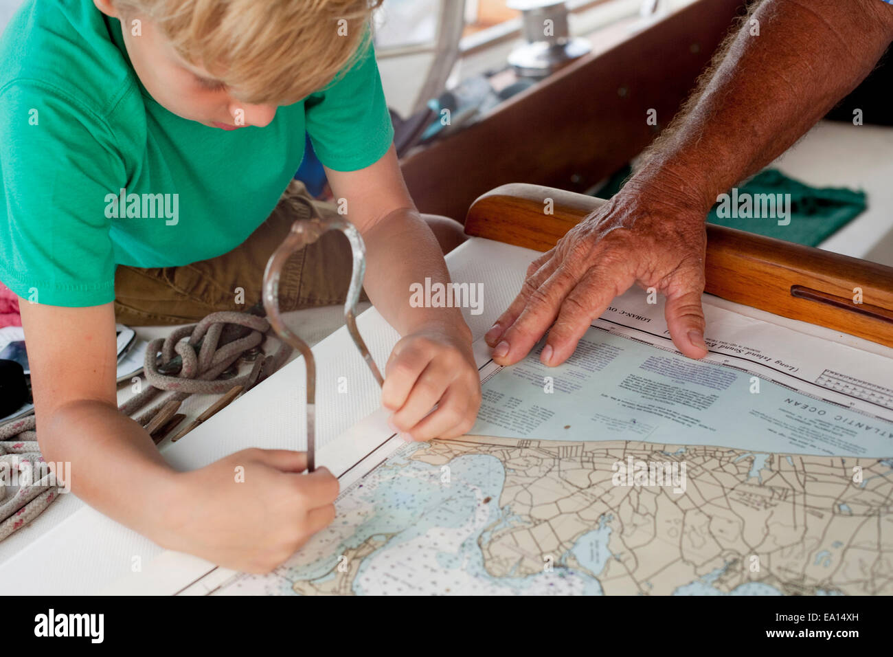 Boy and grandfather using dividers on navigation maps in sailboat cabin - Stock Image