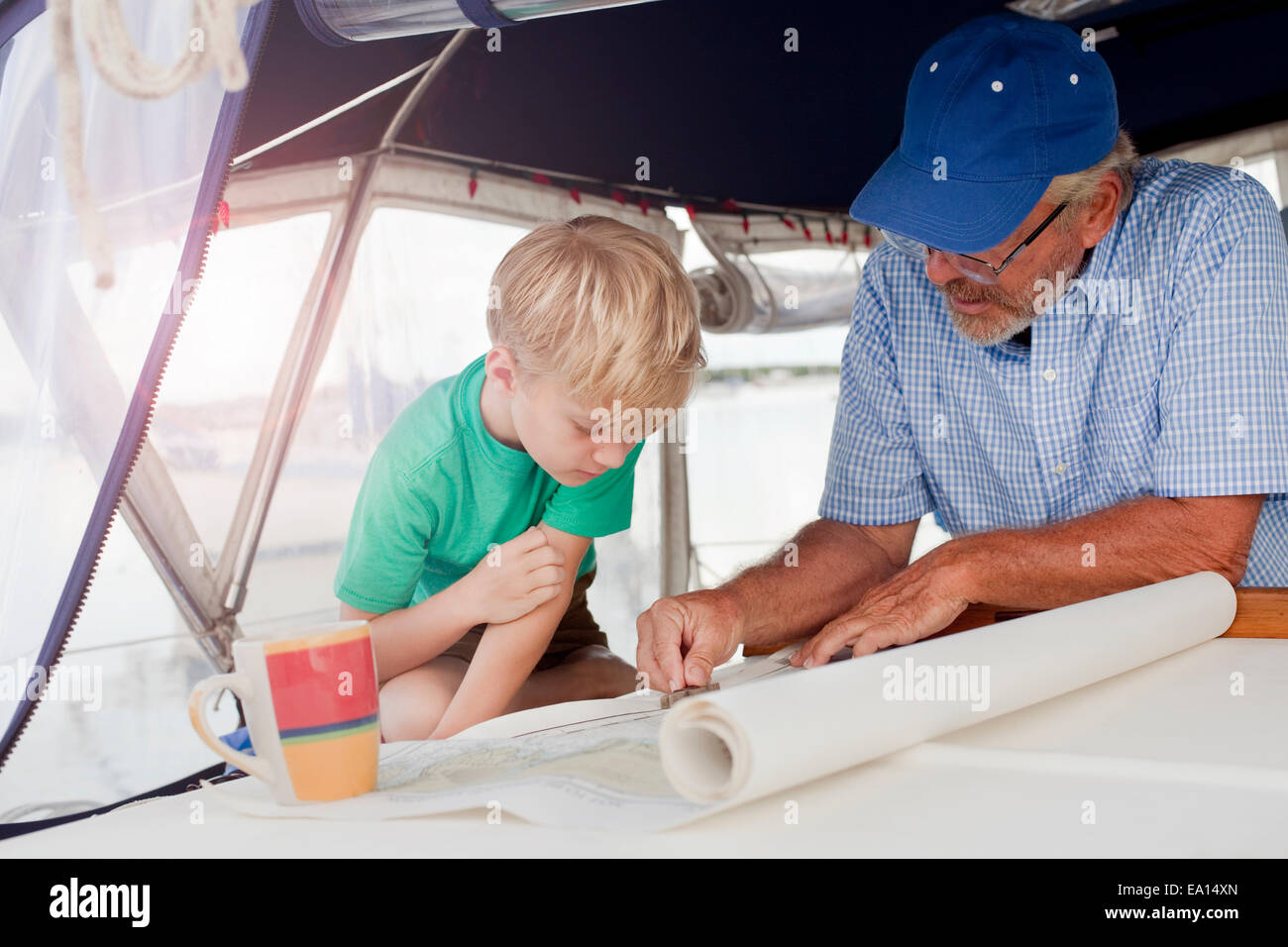 Boy and grandfather planning on navigation maps in sailboat cabin - Stock Image