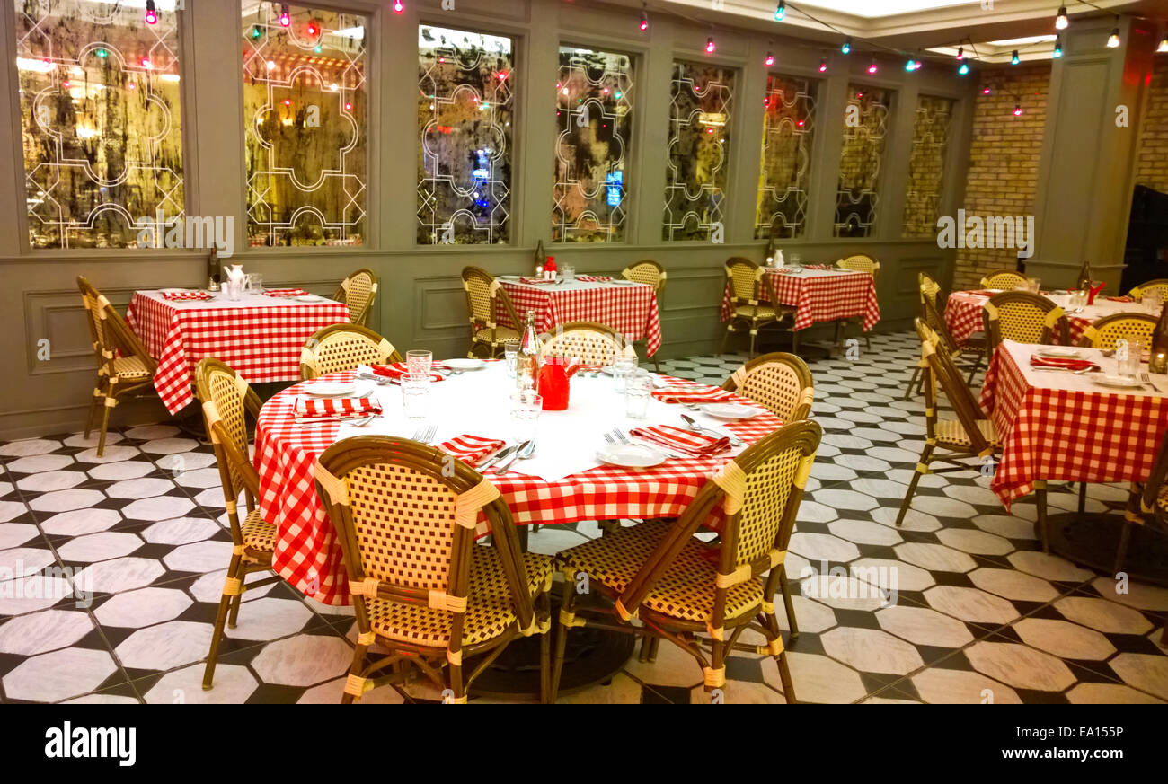 pretty restaurant interior with checkered tablecloths and wicker chairs - Stock Image