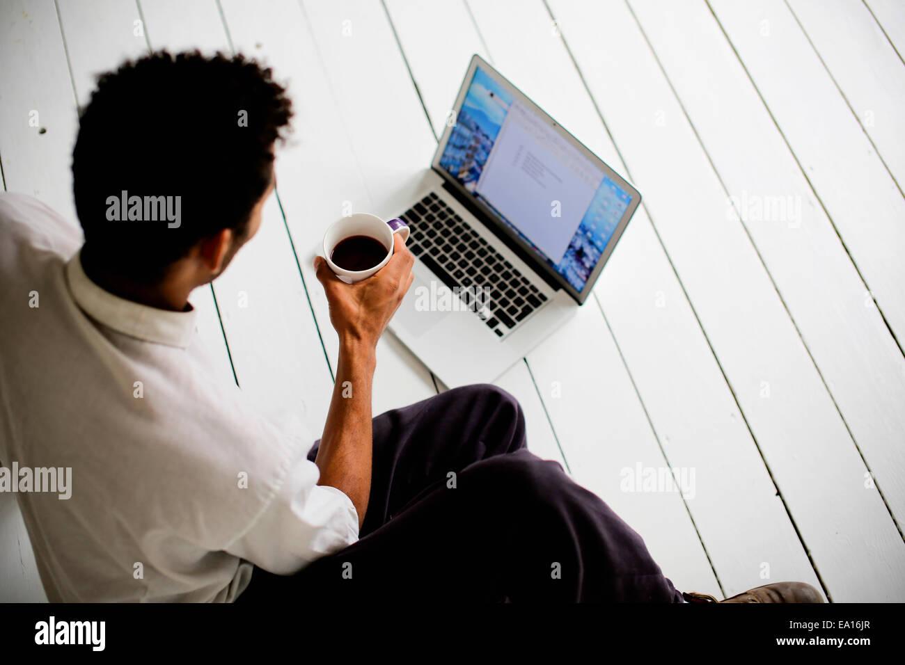 Graphic designer using laptop on floor - Stock Image