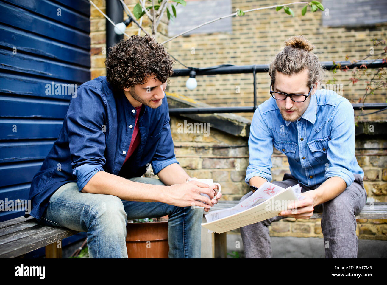 Men having discussion on bench - Stock Image