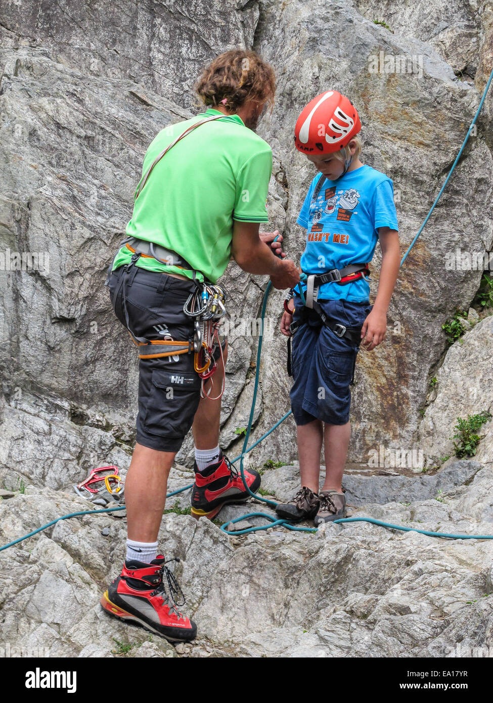 a young boy with his climbing instructor getting ready to climb a EA17YR boy climbing helmet harness stock photos & boy climbing helmet
