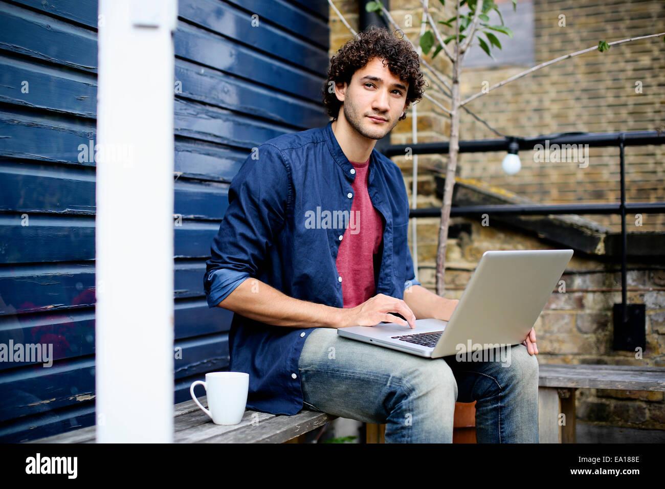 Man using laptop on bench - Stock Image