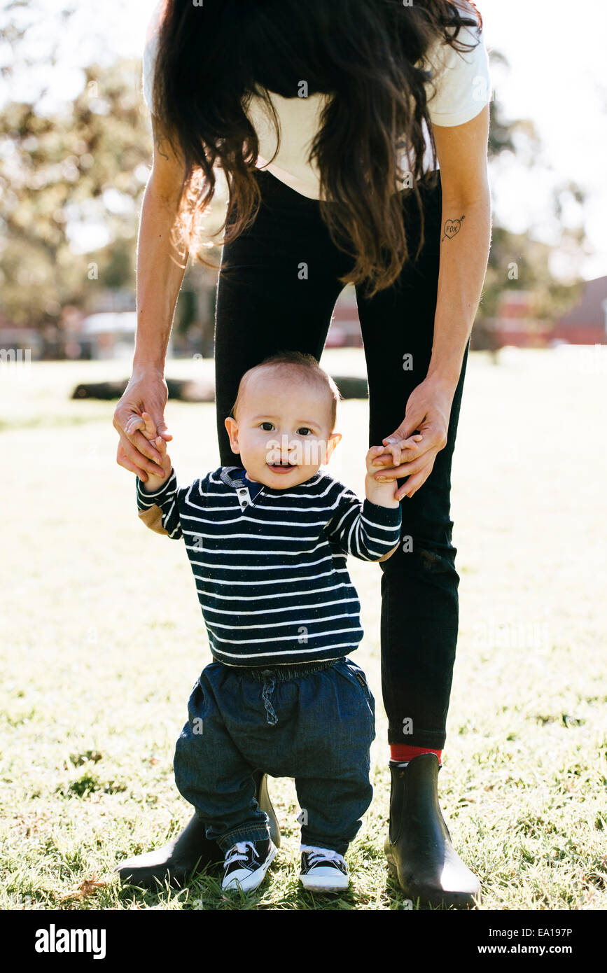 Woman supporting son in first steps - Stock Image