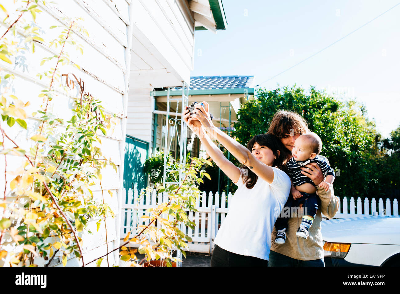 Woman taking family selfie at front of house - Stock Image