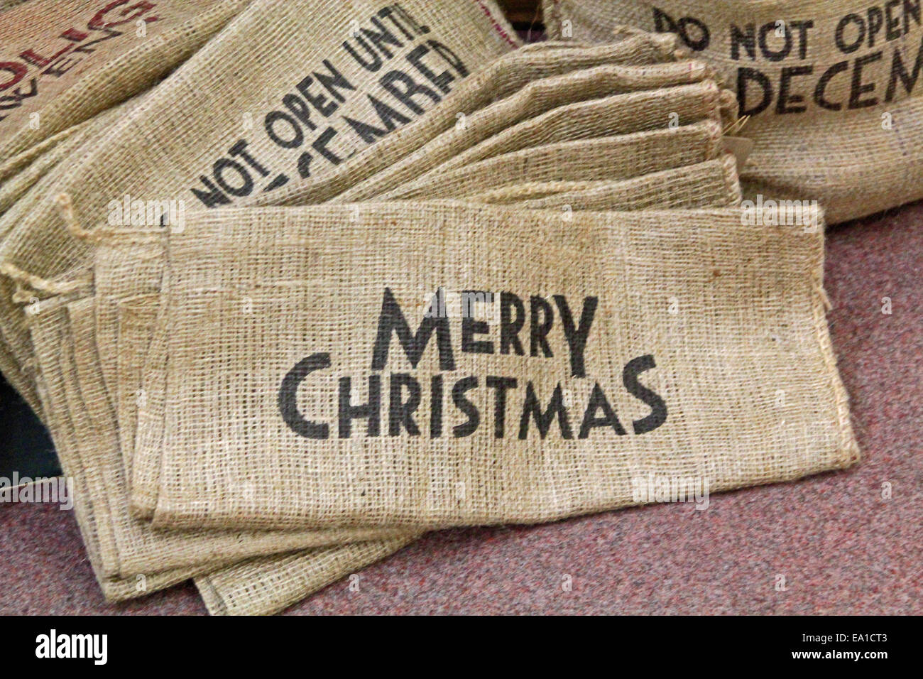 Background pile of sacks with Christmas messages - Stock Image