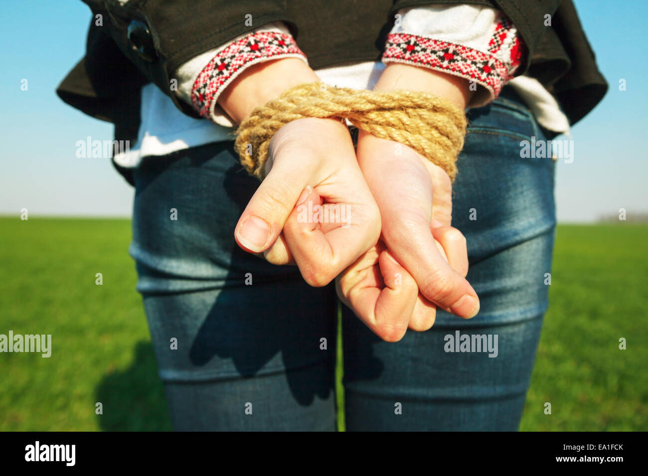 Female hands tied up with the rope Stock Photo