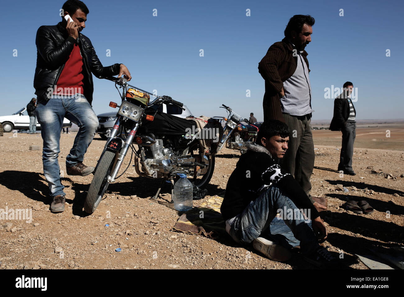 Turkey-Syria border. 5th Nov, 2014. Kurds men watch fighting on the outskirts of Kobani, seen from the Mursitpinar - Stock Image