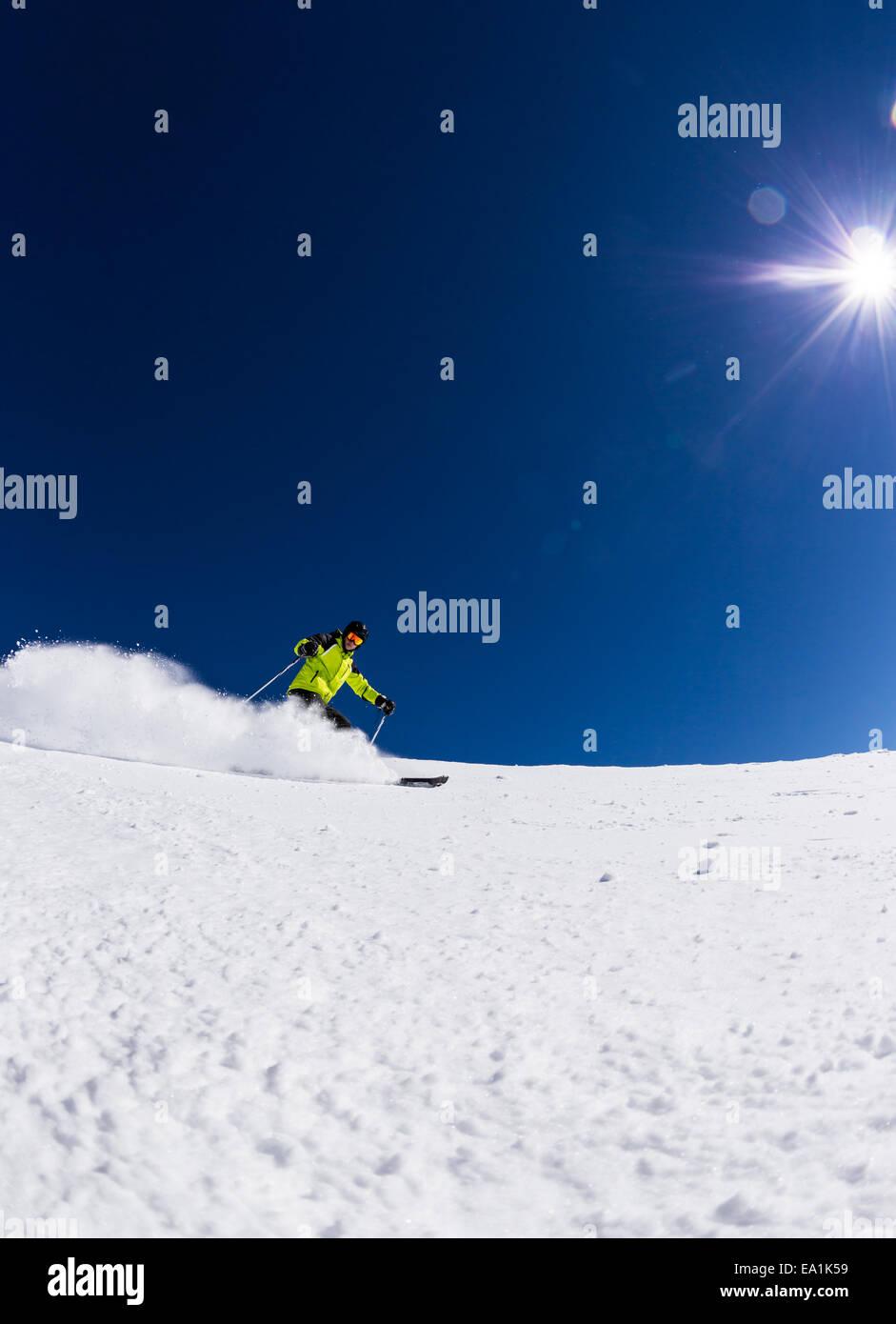 Alpine skier skiing downhill, blue sky on background - Stock Image