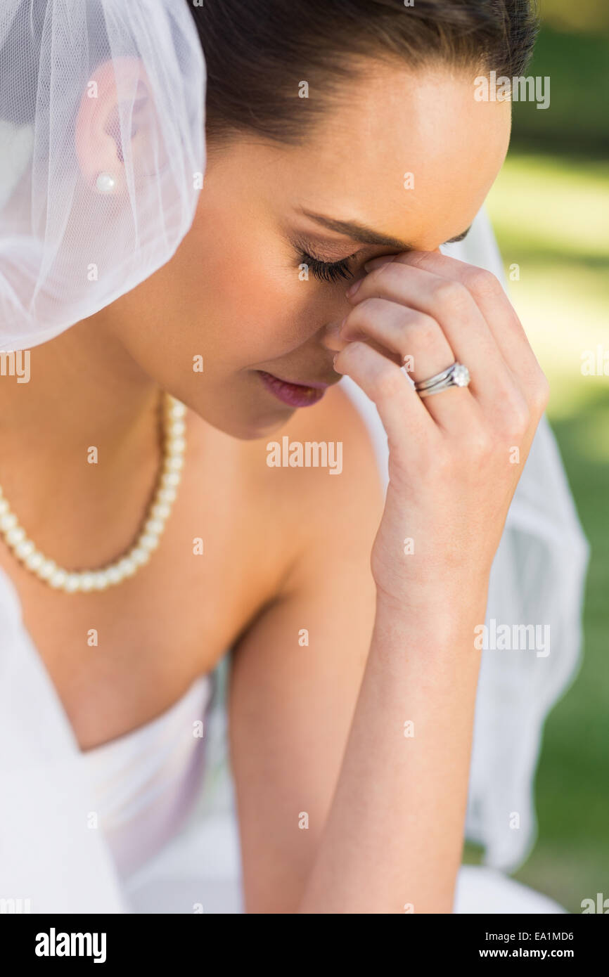 Beautiful worried bride at park - Stock Image
