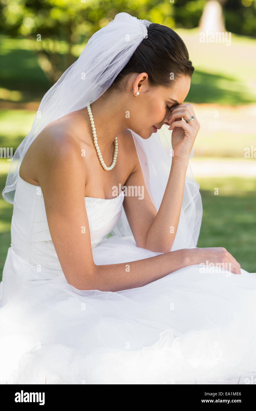 Beautiful worried bride sitting at park - Stock Image