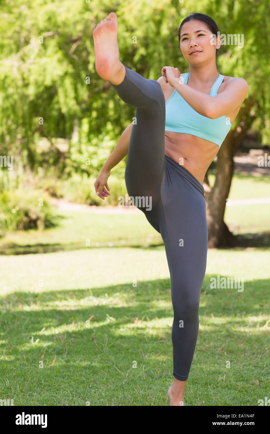 Healthy woman performing air kick in park - Stock Image