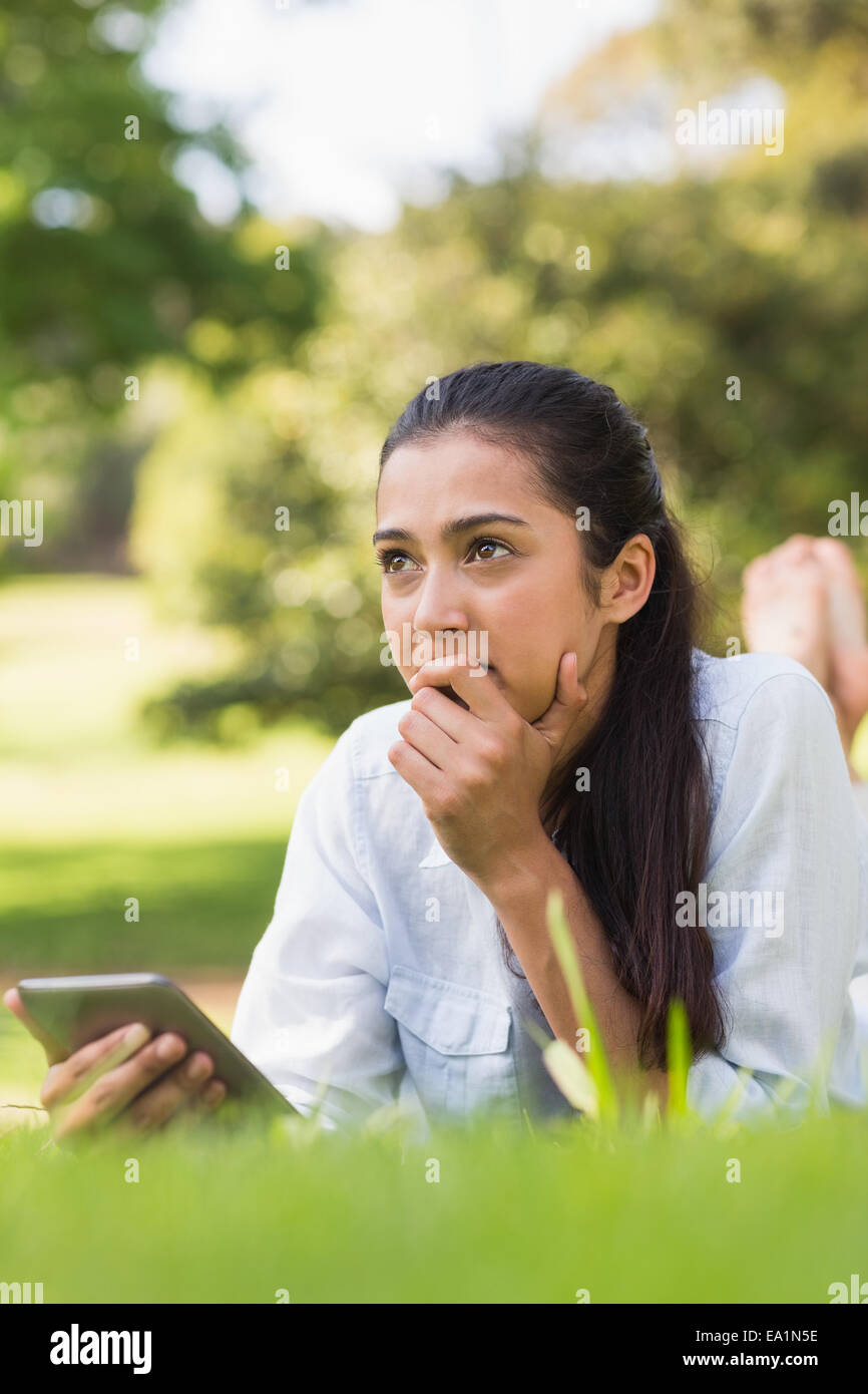 Thoughtful woman text messaging in park - Stock Image