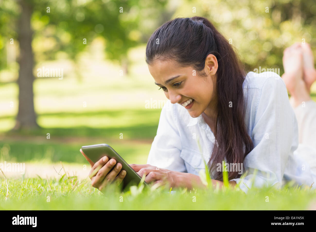 Woman text messaging while relaxing in park - Stock Image
