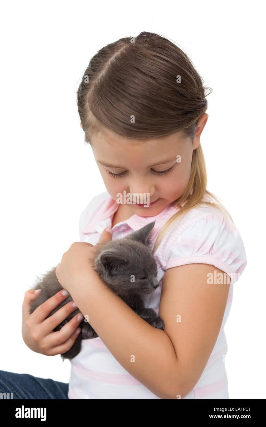 Cute girl cuddling grey kitten - Stock Image