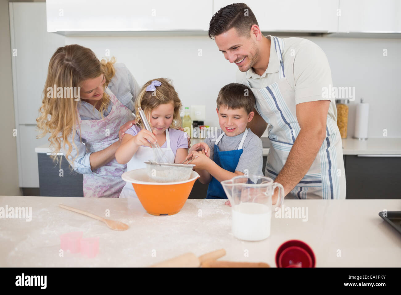 Family preparing cookies at kitchen counter - Stock Image