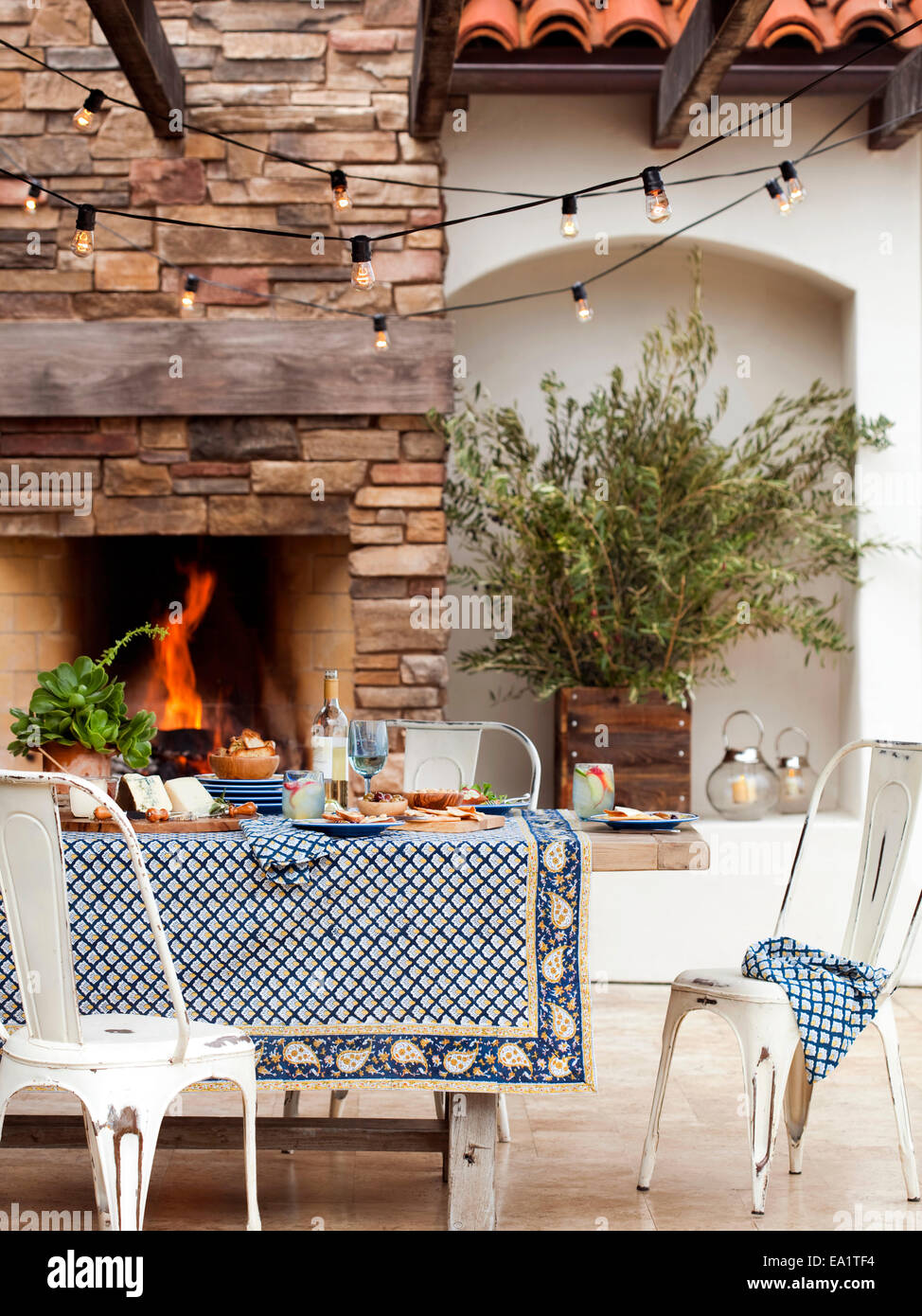 Outdoor dining scene with set table and fire - Stock Image