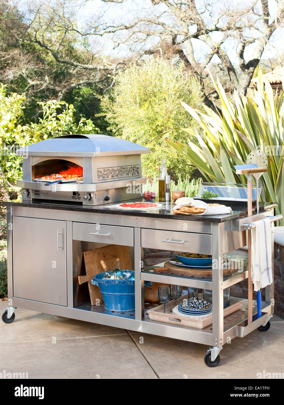 making pizza on an outdoor pizza oven - Stock Image