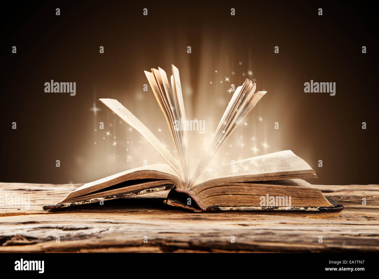 Old book on wooden planks with blur shimmer background - Stock Image