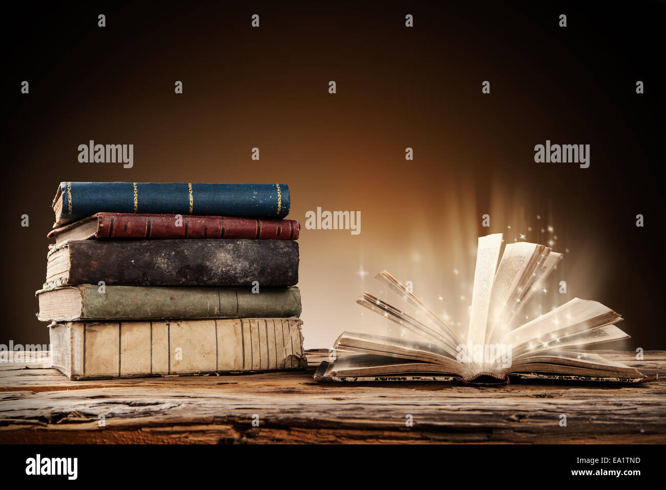 Old books on wooden planks with blur shimmer background - Stock Image