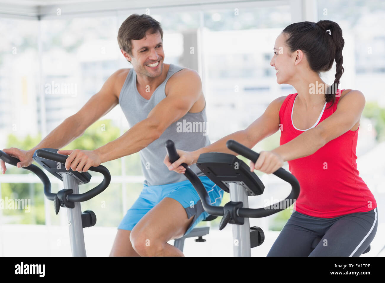 Smiling couple working out at spinning class - Stock Image